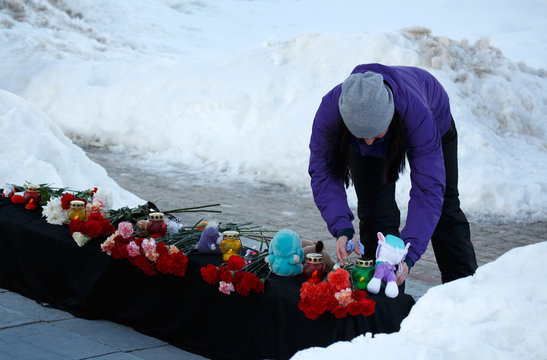 Winter. The girl puts the toy to the mourning memorial
