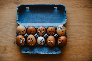 Brown eggs with different faces expressions painted on egg shell. Crazy eggs lying in blue egg carton. Concept of different moods and characters.