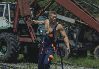 Man, builder or bodybuilder with strict face in overalls.