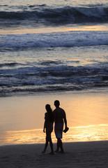 Beautiful couple on the beach at sunset