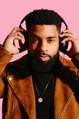 Close up portrait of a cool man with beard holding headphones isolated on pink studio background
