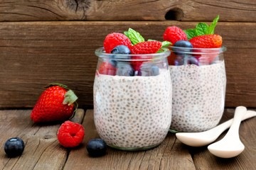 Healthy berry chia pudding in jars. Scene on a rustic wood background.