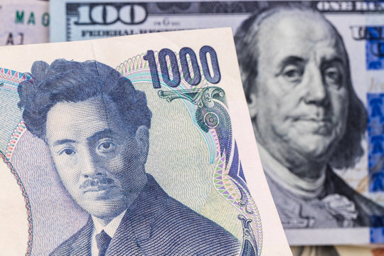 1000 yen with hundred dollar bill on background