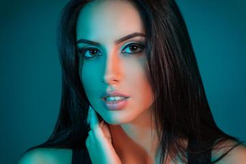 Creative Studio portrait of beautiful female model close-up. The blue lights.