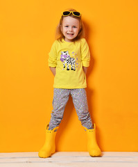 Young child baby  girl kid in yellow rubber boots sunglasses and t-shirt  posing on yellow