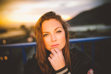 Attractive young woman posing on the street in the nice sunset