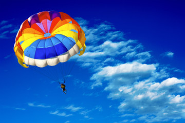 A man is gliding using a parachute on the background of cloudy blue sky.