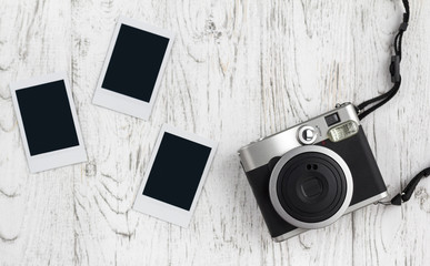 Retro camera and empty old instant paper photo album on wood table. Blank photo frame vintage style