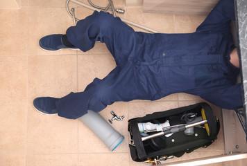 Professional male plumber repairing sink pipes indoors
