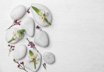 Spa stones and beautiful flowers on wooden background