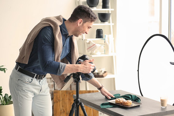 Young man with professional camera preparing food composition in photo studio