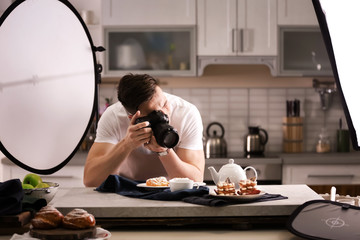 Young man taking picture of food in photo studio