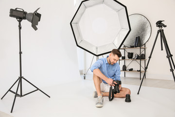 Professional photographer with camera and lighting equipment in studio