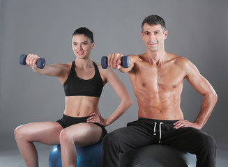 Athletic man and woman with a dumbells