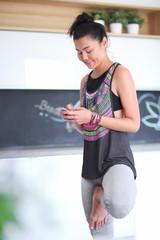 Portrait of a beautiful sports woman using smartphone