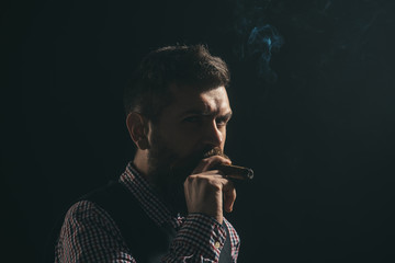 Bearded caucasian man smoking cigar. Serious bearded man in suit smoking cigar. Elegant man with beard and moustache smokes cuban cigar. Businessman has five minute break for smokes. Harmful habit.