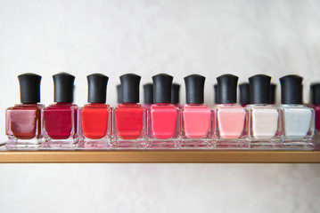 A row of nail polish in various shades of pink and red
