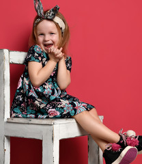 Young cute girl kid happy smiling in modern dress sitting