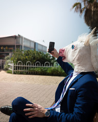 Young unusual man in horse head mask and elegant suit makes a photo by phone. Unicorn is enjoying warm summer day. Strange guy sits on bench
