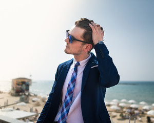 Young man corrects his hair on the background of the sea and sky. Successful businessman in elegant suit and sunglass is relaxing on the nature in warm sunny day. Trendy guy stands on city waterfront