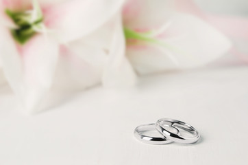Close up of wedding ring with flower on white background