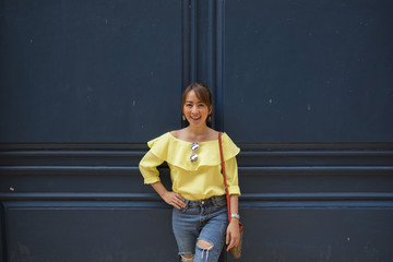 Portrait smile asian girl in yellow dress and jeans stand beside wall blue