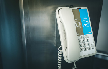 Close up of internal phone or infomation telephone hanging on a pole in the international airport for assistance and help. Airport telephone for emergency call security.