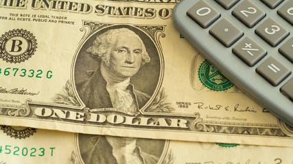 Dollar-Banknoten und ein Taschenrechner liegen auf einem Tisch