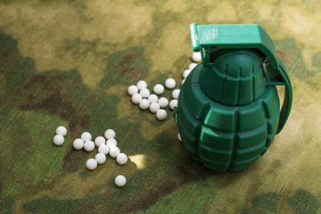 airsoft bbs balls and toy grenade on camouflage background