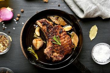 Fried pork steak in frying pan