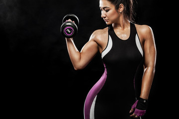 Sporty beautiful woman with dumbbells makes fitness exercising at black background to stay fit