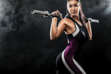 Sporty beautiful woman with barbell makes fitness exercising at black background to stay fit