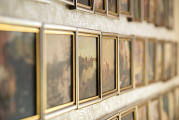 Wall with picture in wooden frames. Classic decoration gallery.