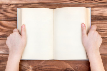 Child's hands holding opened blank book over wooden table. Top view.