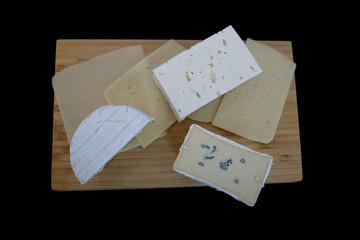 Verschiedene Käsesorten auf einer Holzplatte über schwarzem Hintergrund