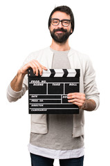 Happy Hipster man holding a clapperboard on white background