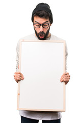 Surprised Hipster man holding an empty placard on white background