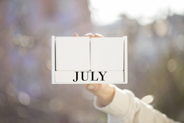 the woman is holding a white wooden calendar. white wooden cube shape calendar for july with hand