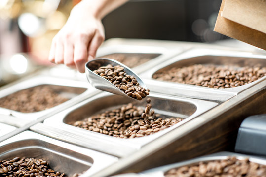 Filling paper bag with coffee beans from the metal trays for selling in the store
