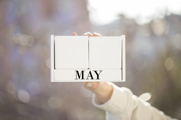 the woman is holding a white wooden calendar. white wooden cube shape calendar for MAY with hand
