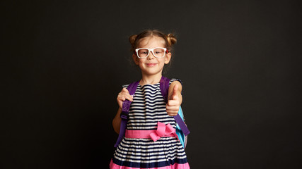 Pretty smiling girl in spectacles wearing backpack, ready for the first school day.  Happy child showing thumb up over studio background.