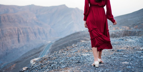 Woman in red dress on a desert mountain top