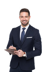 Young caucasian confident businessman writing on clipboard toothy smile isolated