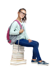 Teenage girl with a school rucksack sitting on a pile of books side view picture