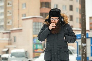 Vape bearded man in real life. Portrait of young guy with large beard in glasses and a black cap vaping an electronic cigarette in the winter.