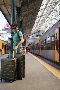 Tourist with luggage on a platform at train station