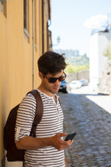 Man checking phone in street on holiday in summer
