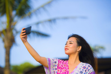 young happy beautiful and gorgeous Asian Chinese woman in glamour dress taking self portrait selfie photo with mobile phone camera at Summer tropical beach resort with palm trees