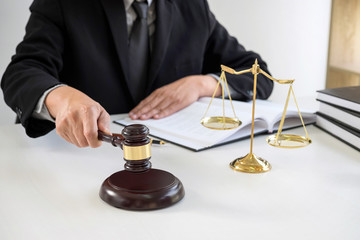 Close up of Male lawyer or judge hand's striking the gavel on sounding block, working with Law books, report the case on table in modern office, Law and justice concept