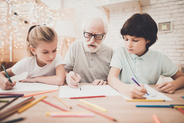 Grandfather, grandson and granddaughter at home. Children are drawing with color pencils.